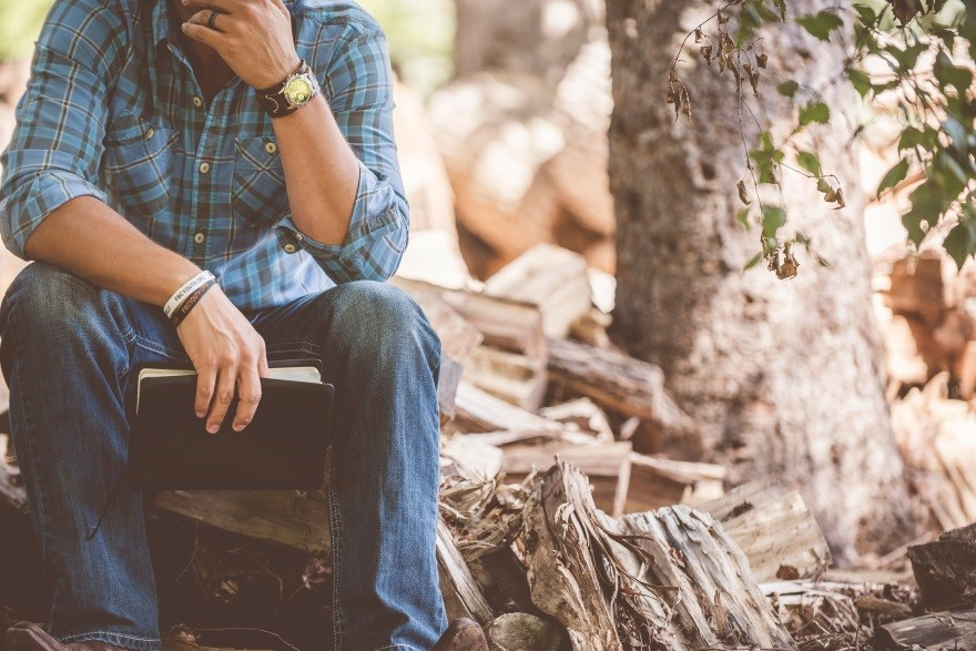 man sitting on wood with bible